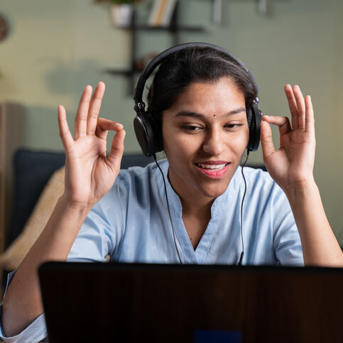 POV shot of young business woman talking to camera by doing namaste gesture - Concept of video chat, conference or vlogging from home by looking at camera